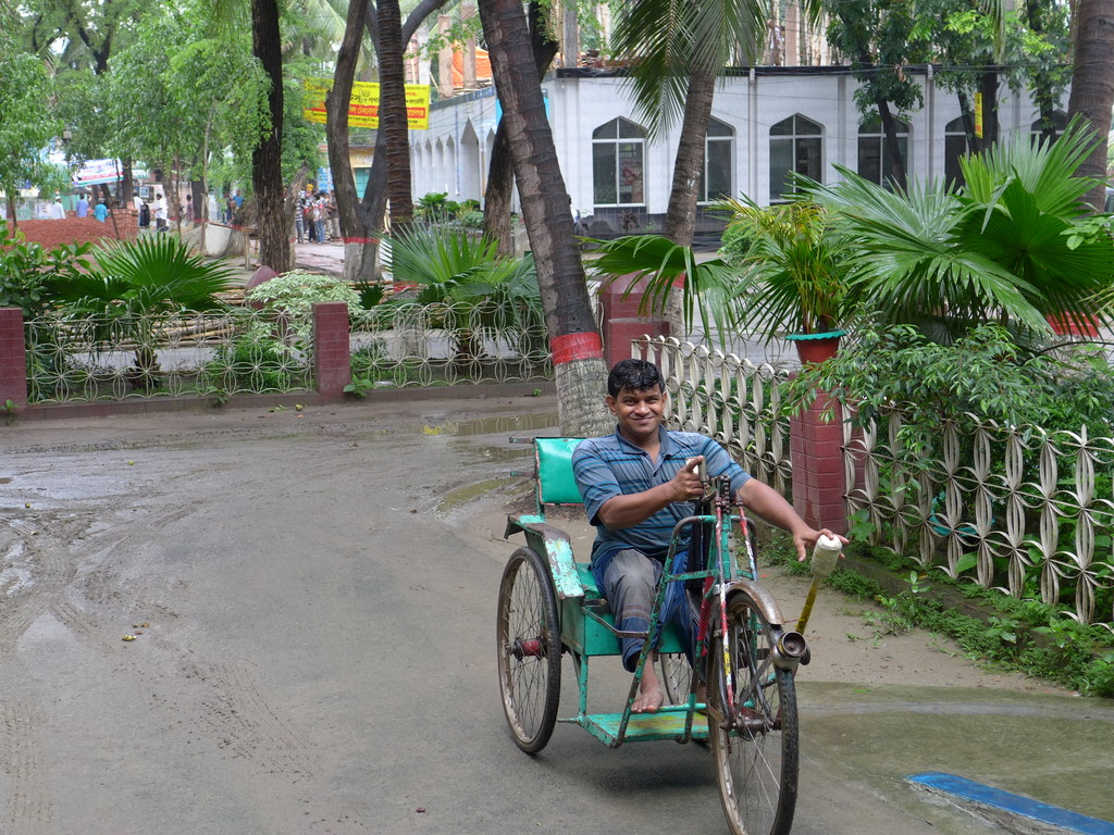 Shiblu comes towards the building in his tricycles. Trees and buildings in the background.