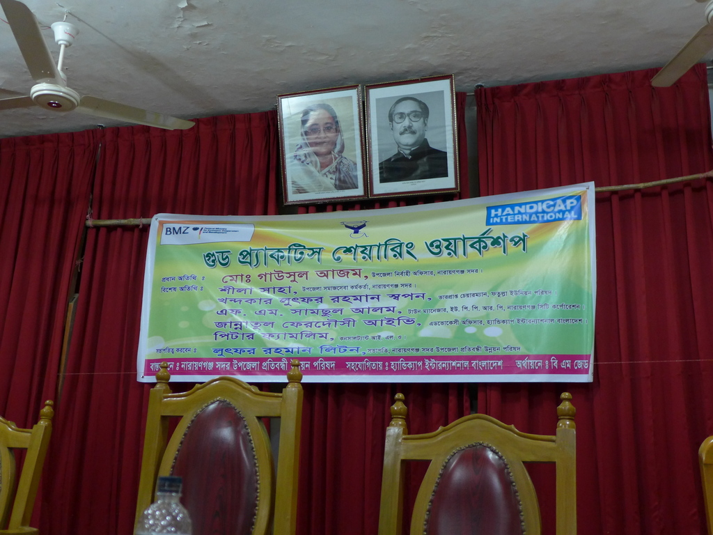 A banner with the workshop title and guests, below portraits of the Prime Minister and her Father.