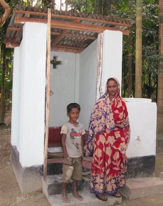A mother and son stand in front of a white latrine. There are two steps to enter, where there is a squat-toilet.