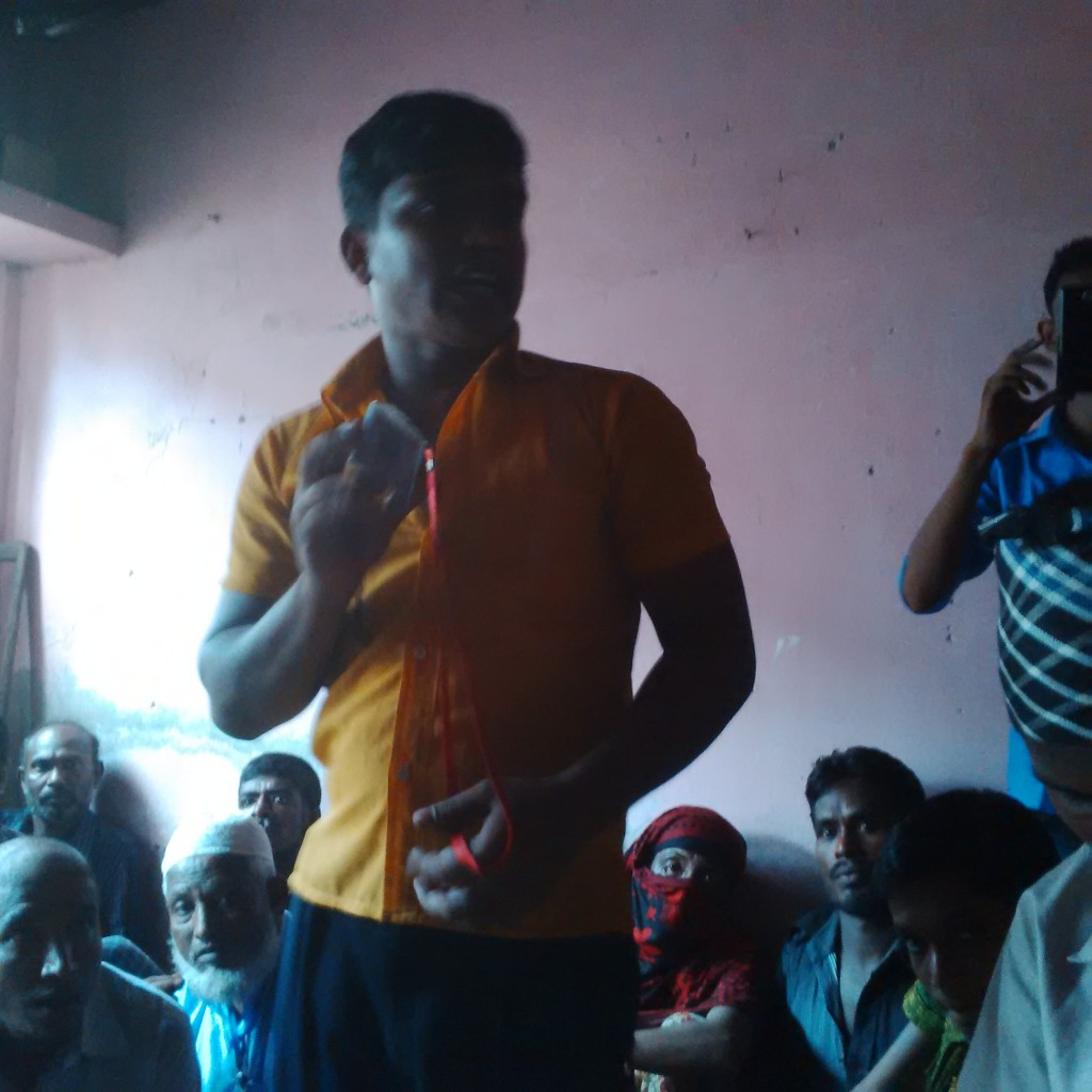 Many people seated in a small room. A man standing in a yellow shirt and gesturing while speaking.