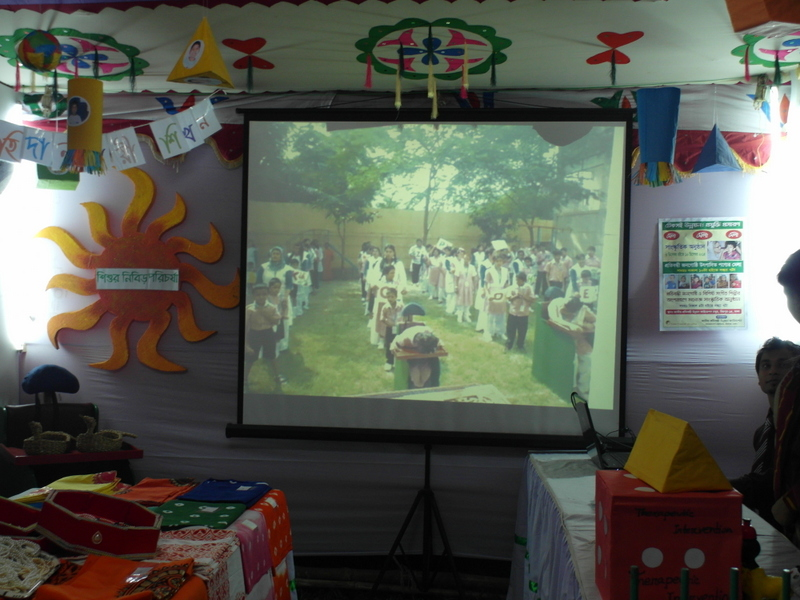 Screen showing children in uniform lined up in a field. On the sides of the screen are hand-made products.