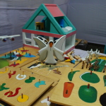 Table with wooden puzzles, a wooden angel and house.