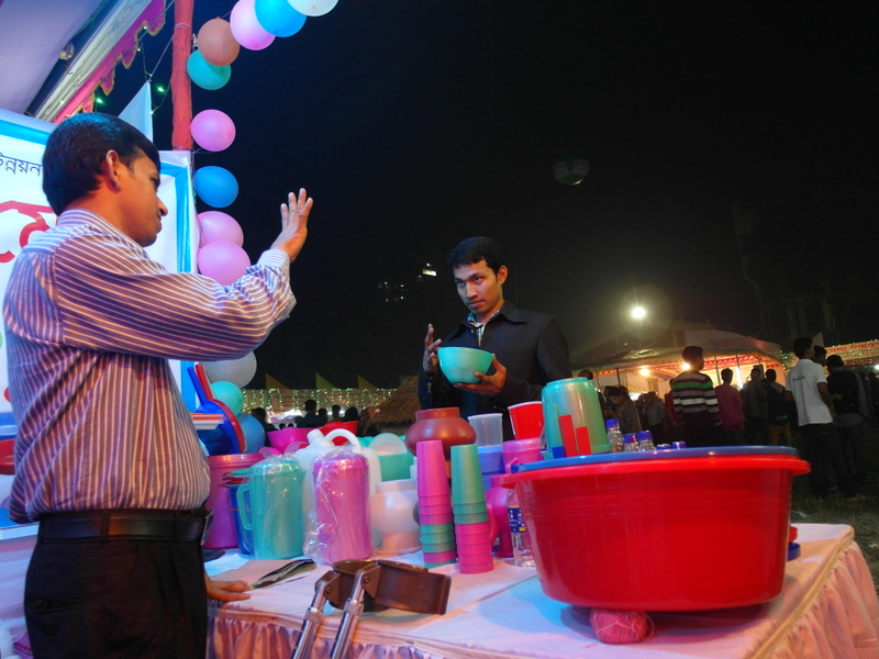 A table with plastic cups, buckets and jugs. Two young men on each side, talking in sign-language.