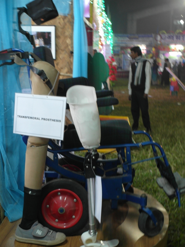 "A wheelchair displayed on a small podium, with two prosthesis in front of it. One of them has a sign that says ""transfemoral prosthesis""."