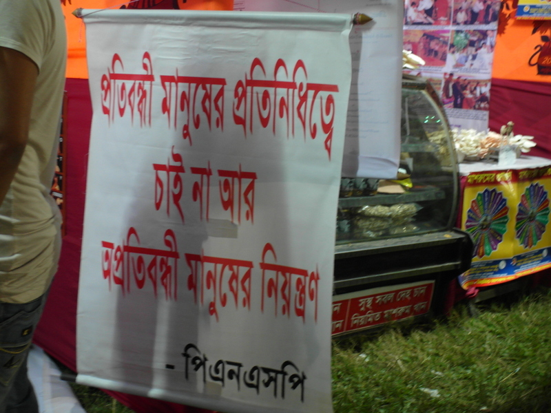 A sign in Bangla hanging at one stall. In the background you can see the mushroom stall.