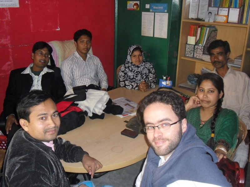 7 people sitting around a table in a small room, looking at the camera.