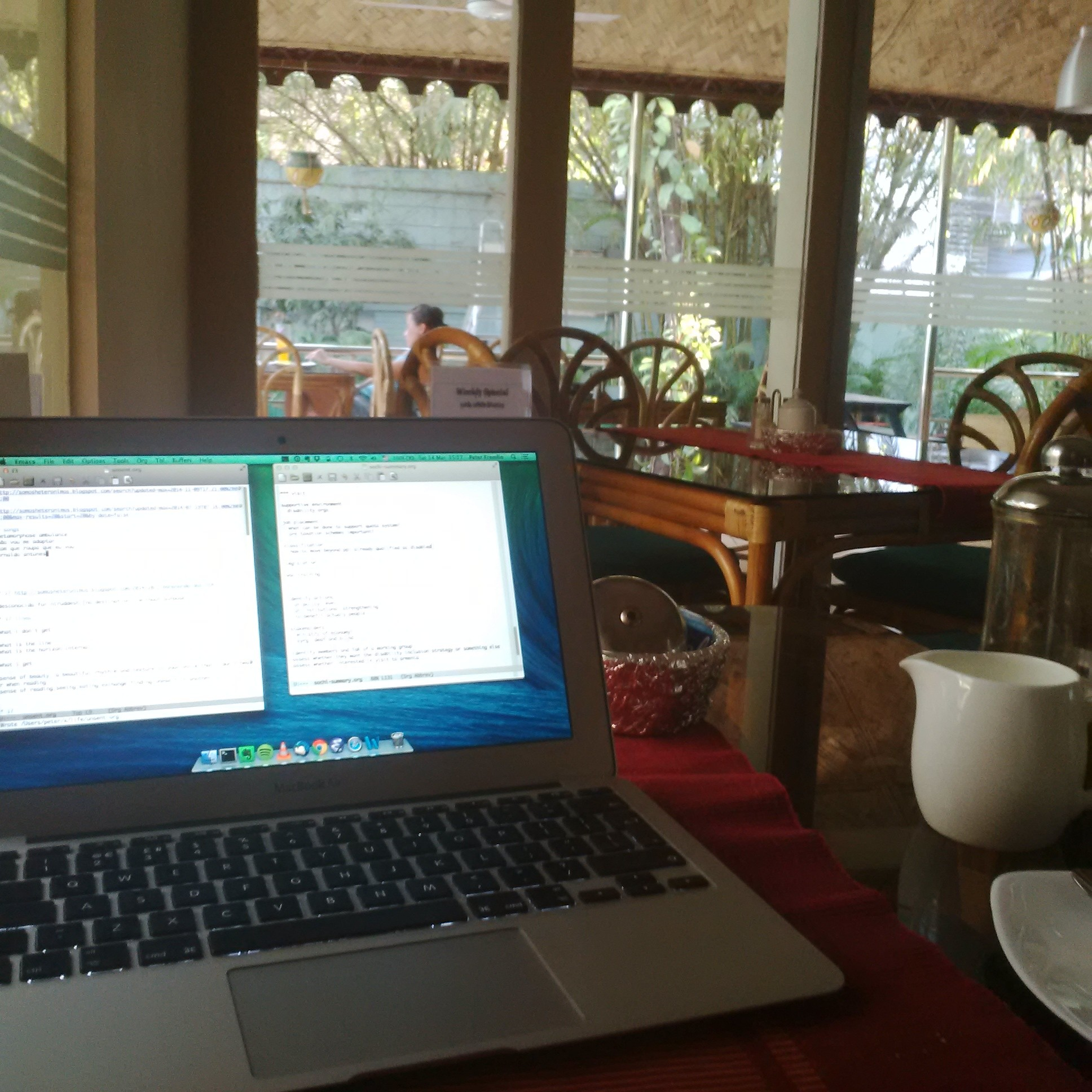 an open laptop on a cafe table with other tables in the background