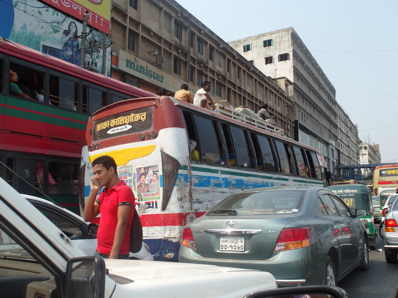 Traffic jam in Dhaka. Background with industrial buildings, buses, people sitting on top of buses. Foreground cars, all stopped, and someone walking between them.