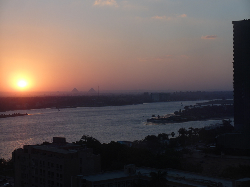 Sunset over the Nile, with two pyramids visible in the background.