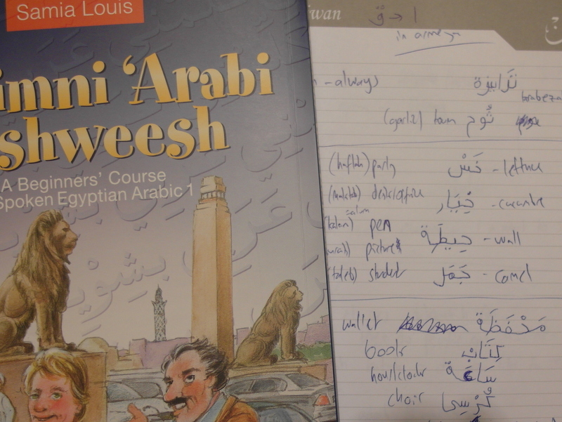 arabic text-book on top of exercise book with arabic words and english translations
